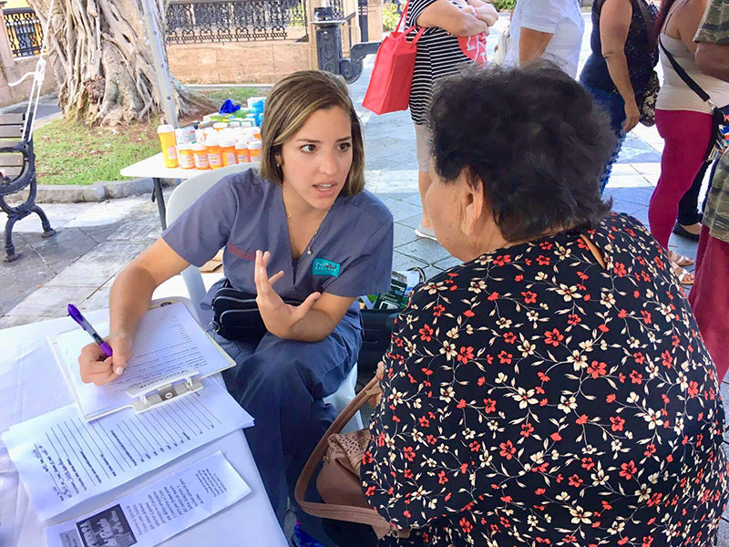 ARIANA HERNANDEZ WITH A PATIENT: Ms. Hernandez at work at one of the clinics. Photo: UMHS Med4You