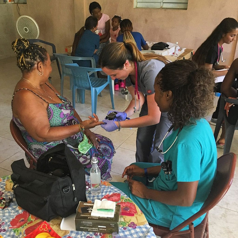 UMHS students Natalie Vera & Charmaine Trotman-Shumantov check a patient's blood sugar in La Caleta, Boca Chica, Dominican Republic. Photo: UMHS Med4You