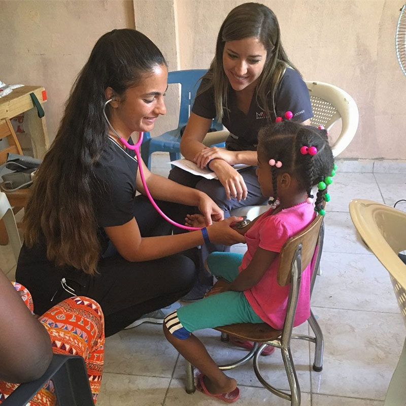 UMHS students (left to right) Paola Mora & Ariana Hernandez examine a young patient in La Caleta, Boca Chica, Dominican Republic. Photo: UMHS Med4You