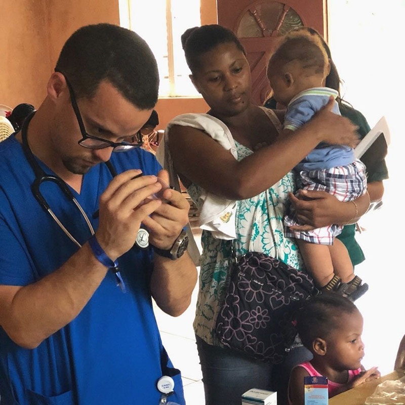 Luis Adorno, UMHS Med4You Chapter President, at work while patients wait at the La Caleta, Boca Chica clinic in the Dominican Republic. Mr. Adorno was the student leader & worked very hard in fundraising for the benefit of this community. Photo: UMHS Med4You