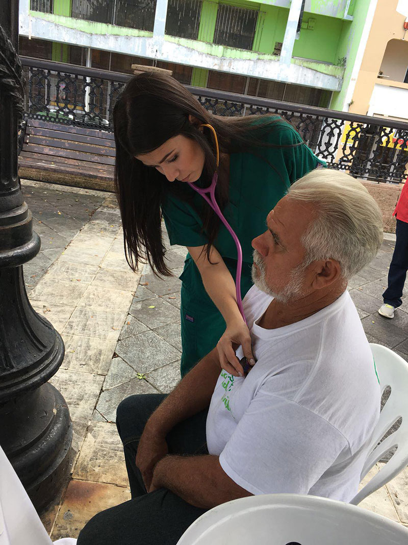 Fabiola Ramos (UMHS EBS5 student/Med4You member) helps a patient during the Arecibo, Puerto Rico free health clinic. Photo: UMHS Med4You