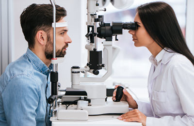 Female Optometrist with patient doing an eye health exam