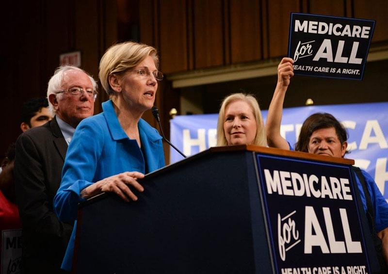DEMOCRATS FOR 'MEDICARE FOR ALL': Senator Elizabeth Warren (D-MA) speaks in 2017 about single-payer healthcare as Senator Bernie Sanders (I-VT) listens in background. Photo: Senate Democrats/Wikimedia Commons