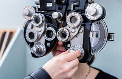 eye examination with a phoropter performed by an optometrist or an ophthalmologist