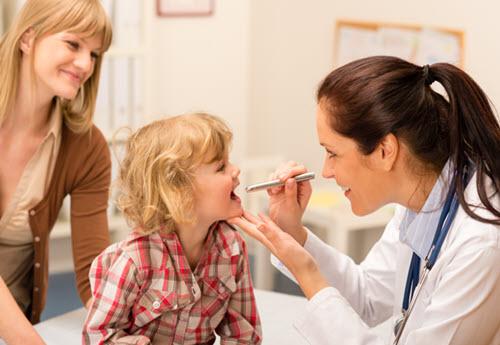 female pediatric specialist examining a child